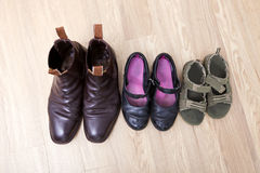 High angle view of family shoes placed in a row on hardwood floor Royalty Free Stock Images