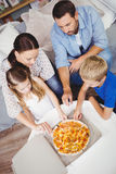High angle view of family taking pizza slices Royalty Free Stock Photo
