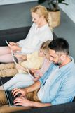 High angle view of family with two kids sitting on sofa and using digital devices. At home stock images