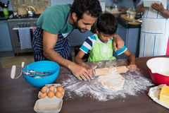 High angle view father assisting son for rolling dough. High angle view of father assisting son for rolling dough with men background Royalty Free Stock Photography