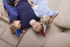 High angle view of father and children with artificial mustache and party hat sleeping on sofa bed Royalty Free Stock Image
