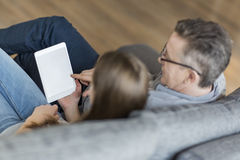 High angle view of father and daughter using digital tablet on sofa Royalty Free Stock Photo