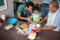 High angle view of father and grandfather looking at boy making food. While standing in kitchen at home Stock Photo
