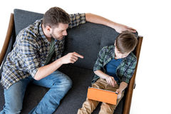 High angle view of father sitting on sofa and pointing with finger at son using digital tablet Stock Image
