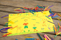High angle view of fathers day greeting card amidst crayons on table royalty free stock photography