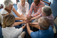 High angle view of female doctor amidst seniors stacking hands. At retirement home royalty free stock image