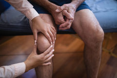 High angle view of female therapist examining knee while senior male patient sitting on bed Stock Images