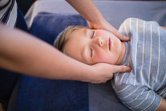 High angle view of female therapist giving neck massage to boy Royalty Free Stock Images