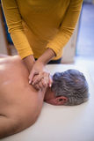High angle view of female therapist giving neck massage to shirtless male patient Royalty Free Stock Photo