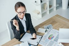 High angle view of financier working at table in office. And using smartphone stock images