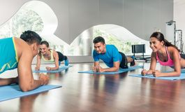 High-angle view of a fitness instructor during group calisthenics class. High-angle view of a fitness instructor motivating three young people to exercise Royalty Free Stock Images