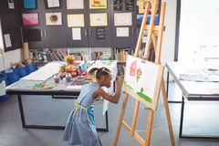 High angle view of focused girl painting on canvas. In classroom royalty free stock images
