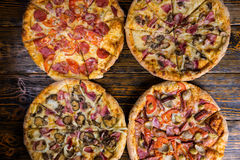 High angle view of four different pizzas on wooden table Royalty Free Stock Photo