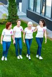 High angle view of four smiling women with breast cancer awareness ribbons walking. Together stock photo