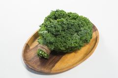 High angle view of fresh kale bundle in wooden plate. On white background Stock Images
