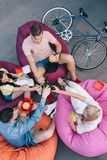 high angle view of friends clinking with bottles of beer and holding fast food on bean stock photo
