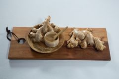 High angle view of ginger and powder in wooden plate on serving board. Over white background Stock Image