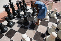 High angle view of girl bending by chess pieces Royalty Free Stock Image