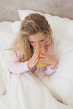 High angle view of girl drinking orange juice in bed Stock Photo