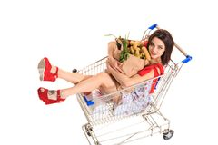 High angle view of girl smiling at camera while holding grocery bags and sitting in shopping trolley isolated on white. Brunette in a short summer dress and Royalty Free Stock Photos