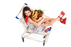 High angle view of girl smiling at camera while holding grocery bags and sitting in shopping trolley isolated on white. Brunette in a short summer dress and Royalty Free Stock Images