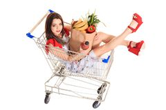 High angle view of girl smiling at camera while holding grocery bags and sitting in shopping trolley isolated on white. Brunette in a short summer dress and Stock Photo