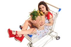 High angle view of girl smiling at camera while holding grocery bags and sitting in shopping trolley isolated on white. Brunette in a short summer dress and Royalty Free Stock Image