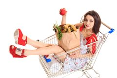 High angle view of girl smiling at camera while holding grocery bags and sitting in shopping trolley isolated on white. Brunette in a short summer dress and Stock Image