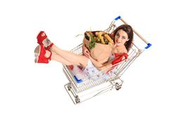 High angle view of girl smiling at camera while holding grocery bags and sitting in shopping trolley isolated on white. Brunette in a short summer dress and Royalty Free Stock Photo