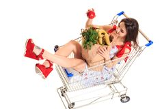 High angle view of girl smiling at camera while holding grocery bags and sitting in shopping trolley isolated on white. Brunette in a short summer dress and Stock Photography