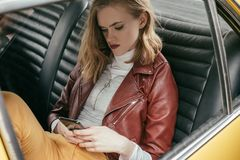High angle view of girl using smartphone. In vintage car stock images