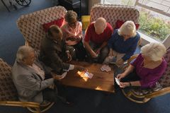 Group of senior friends playing cards at nursing home royalty free stock photography
