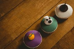 High angle view of Halloween cup cakes arranged on table. High angle view of Halloween cup cakes arranged on wooden table Royalty Free Stock Photography