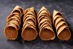 High angle view of hand made waffle ice cream cones in a row, selective focus. High angle view of hand made waffle ice cream cones in a row, on a black royalty free stock images
