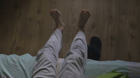 High angle view of a handsome man waking up and putting on slippers stock video