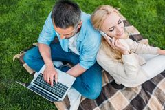 High angle view of happy couple using smartphone and laptop. In park royalty free stock photos