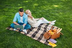 High angle view of happy couple using smartphone and laptop while sitting on plaid. At picnic royalty free stock image