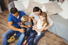 High angle view of happy family sitting by sofa Stock Images