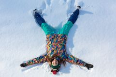 High angle view of happy girl lying on snow and moving her arms and legs up and down creating a snow angel figure. Smiling woman lying on snow in winter royalty free stock photo