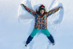 High angle view of happy girl lying on snow and moving her arms and legs up and down creating a snow angel figure. Smiling woman lying on snow in winter royalty free stock images