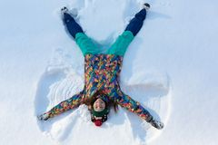 High angle view of happy girl lying on snow and moving her arms and legs up and down creating a snow angel figure. Smiling woman lying on snow in winter stock photos