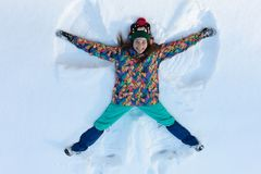 High angle view of happy girl lying on snow and moving her arms and legs up and down creating a snow angel figure. Smiling woman lying on snow in winter royalty free stock image