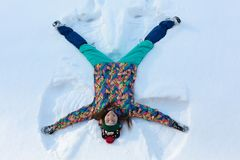 High angle view of happy girl lying on snow and moving her arms and legs up and down creating a snow angel figure. Smiling woman lying on snow in winter royalty free stock photos