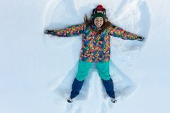 High angle view of happy girl lying on snow and moving her arms and legs up and down creating a snow angel figure. Smiling woman lying on snow in winter stock image