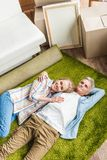 high angle view of happy senior couple lying on carpet in new stock image