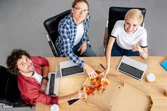 High angle view of happy young colleagues eating pizza and smiling at camera. At workplace royalty free stock photography