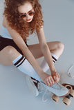 High angle view of hipster girl in sunglasses wearing roller skates sitting. On grey Royalty Free Stock Photo