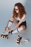 High angle view of hipster girl in sunglasses wearing roller skates sitting. On grey Royalty Free Stock Photos