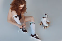 High angle view of hipster girl in sunglasses wearing roller skates sitting. On grey Royalty Free Stock Images