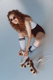 High angle view of hipster girl in sunglasses wearing roller skates sitting. On grey Stock Photography